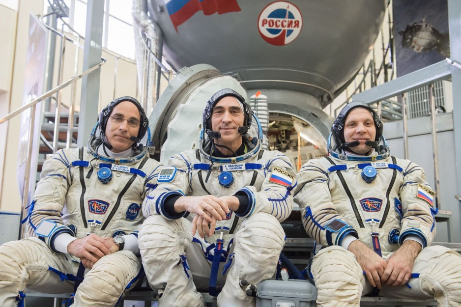 The three astronauts set to launch on April 9 in space suits, in front of their launch vehicle a Soyuz spacecraft