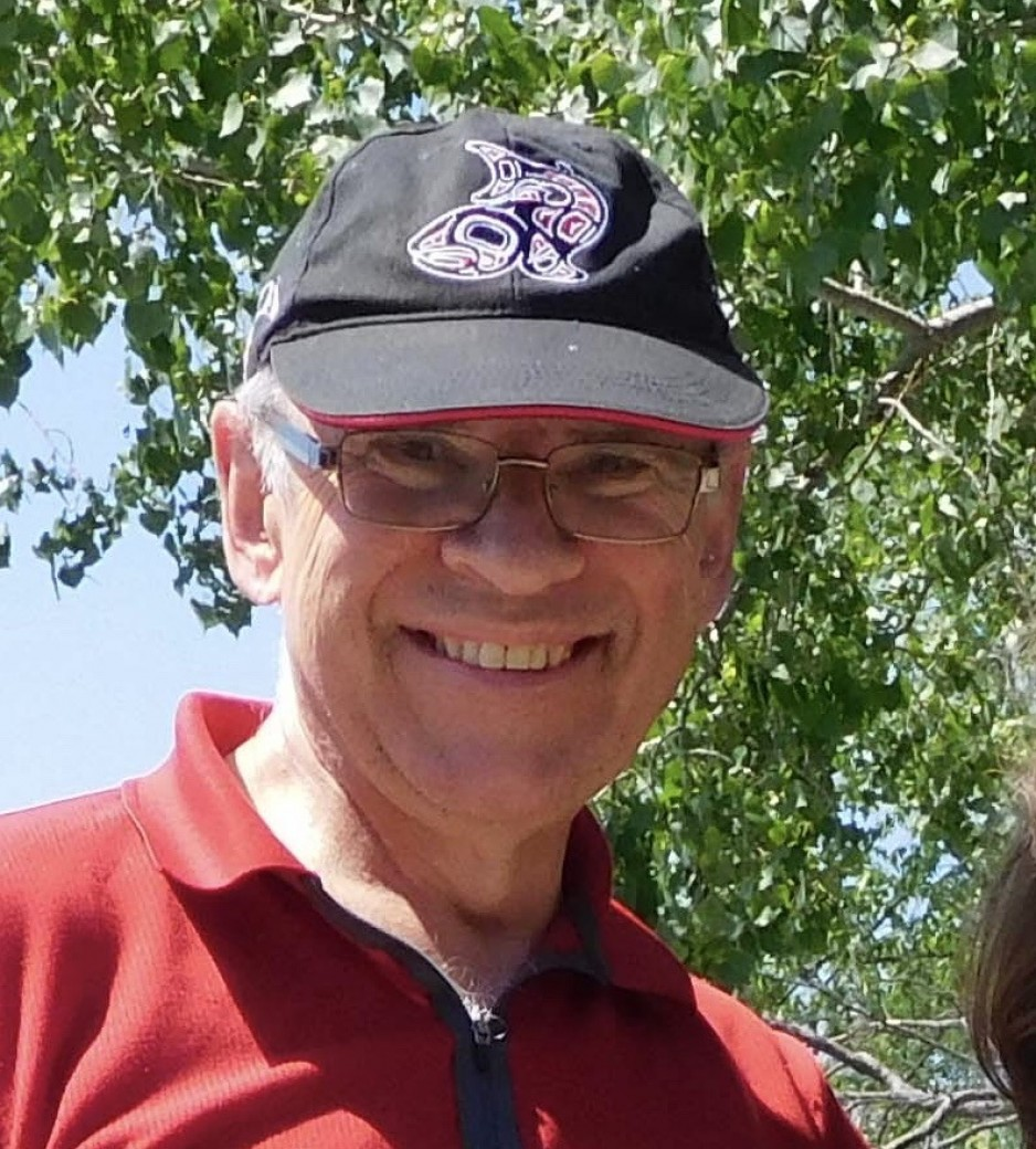 A man in a red shirt and ball cap smiles warmly at the camera.