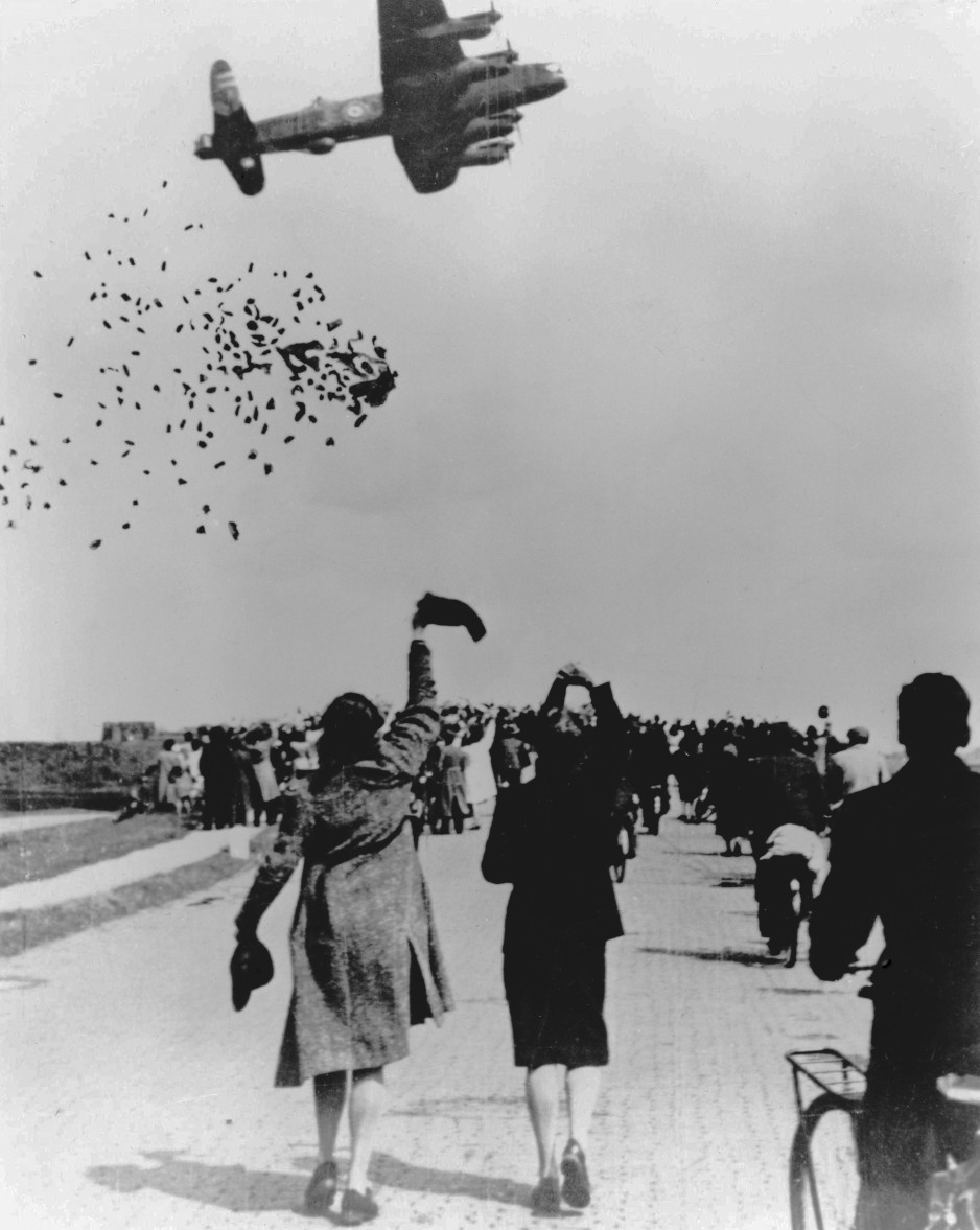 A black-and-white image depicts food packages falling from a low-flying aircraft; people are running towards the falling cargo. Wikimedia Commons