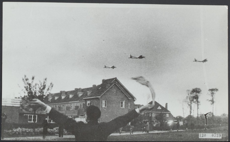 A black-and-white image shows a person waving a white cloth overhead while watching planes fly low over a residential area. Wikimedia Commons
