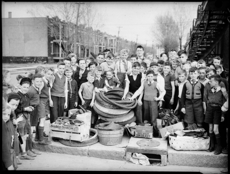 A large group of children, mostly young boys, and a man, are gathered in a semi-circle on a suburban sidewalk, surrounding a pile of car and bicycle tires, and rubber boots which they had collected.