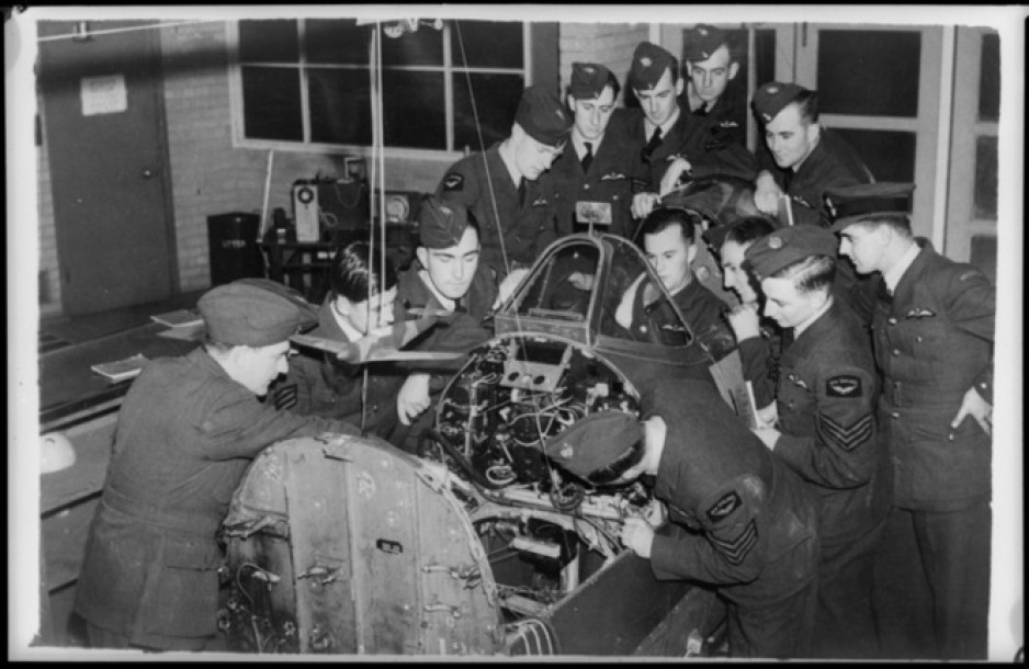 A group of men in air force uniforms surround the detached cockpit section of a Spitfire, looking at how its controls operate.