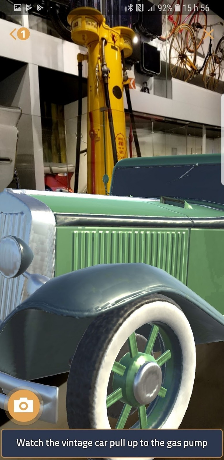 A moving image of a vintage green car appears on a phone screen after someone has found the gas pump in the museum.