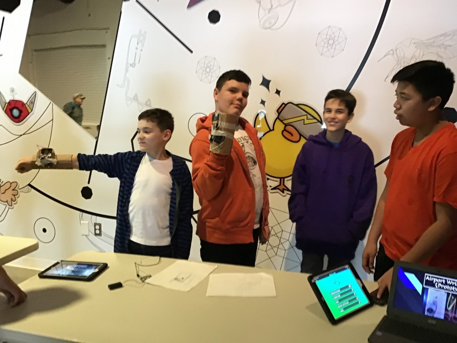 Four boys show off their inventions to museum guest. They have invented wristbands to help people move through airports. Two boys model their prototypes, which are made from cardboard and circuitry.