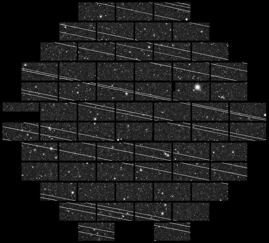 An image of the night sky, with many individual stars visible. There are a large number of white streaks going across the image, created by the Starlink satellites flying through the frame.