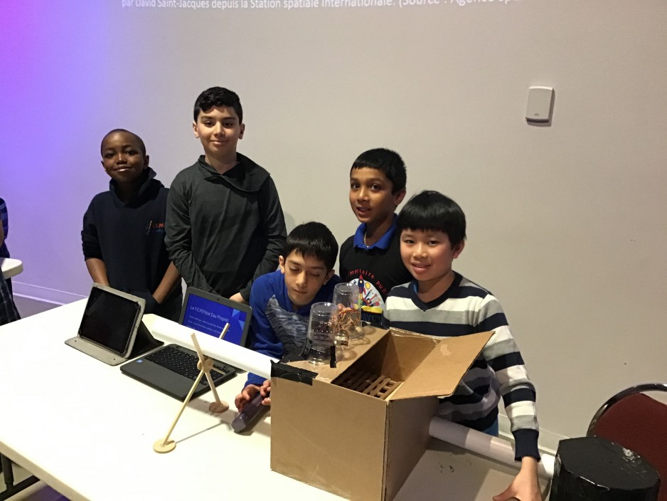 5 boys show off their invention to museum visitors. In front of them are a computer and a cardboard box with several attachments and wires coming out