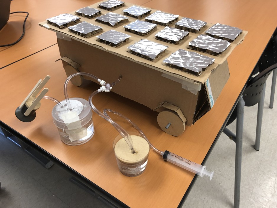 A cardboard box with wheels and grey solar panels above is shown, along with two cylinder hydraulic system.