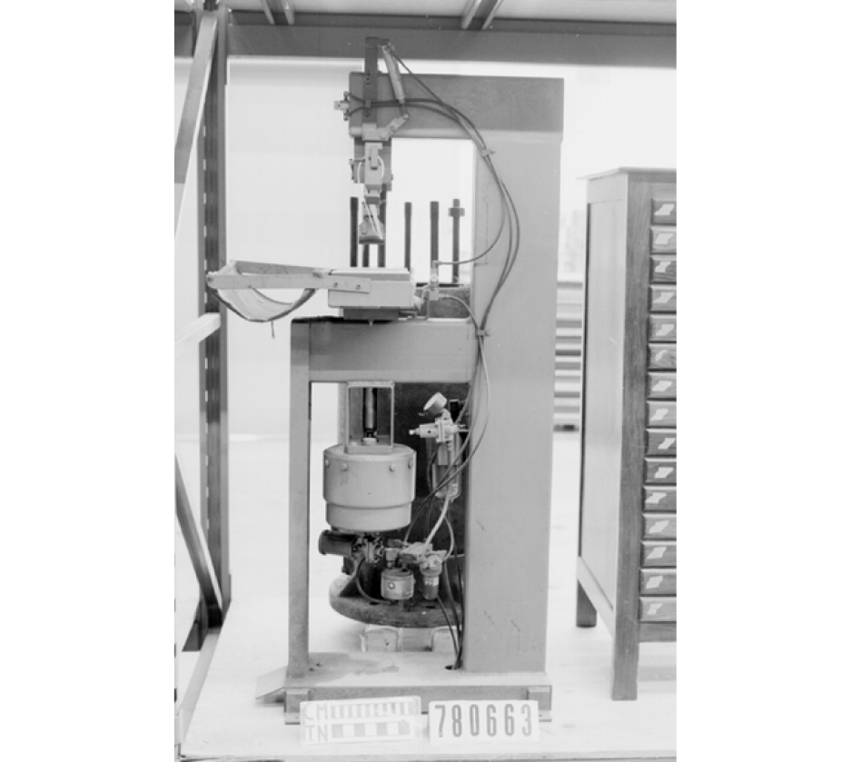 A black-and-white image of a small machine, used in the 1950s to make manipulate metal