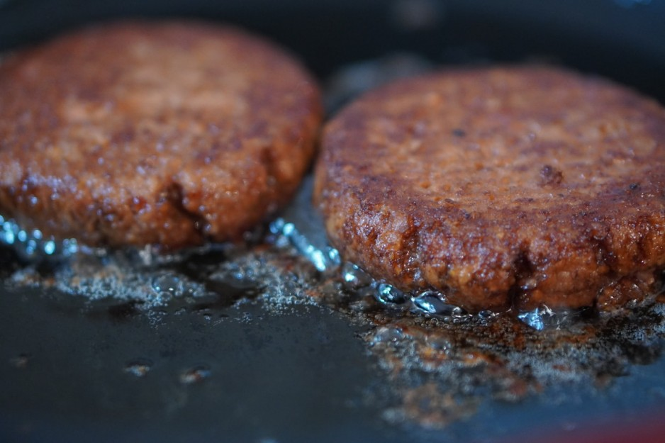 A close-up image of two burger patties cooking in a pan.