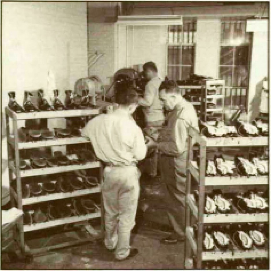A black-and-white image shows three men are standing in a room filled with shelves of shoes. One of the men is working with a shoe press at the back of the room. Bars are visible in the windows.