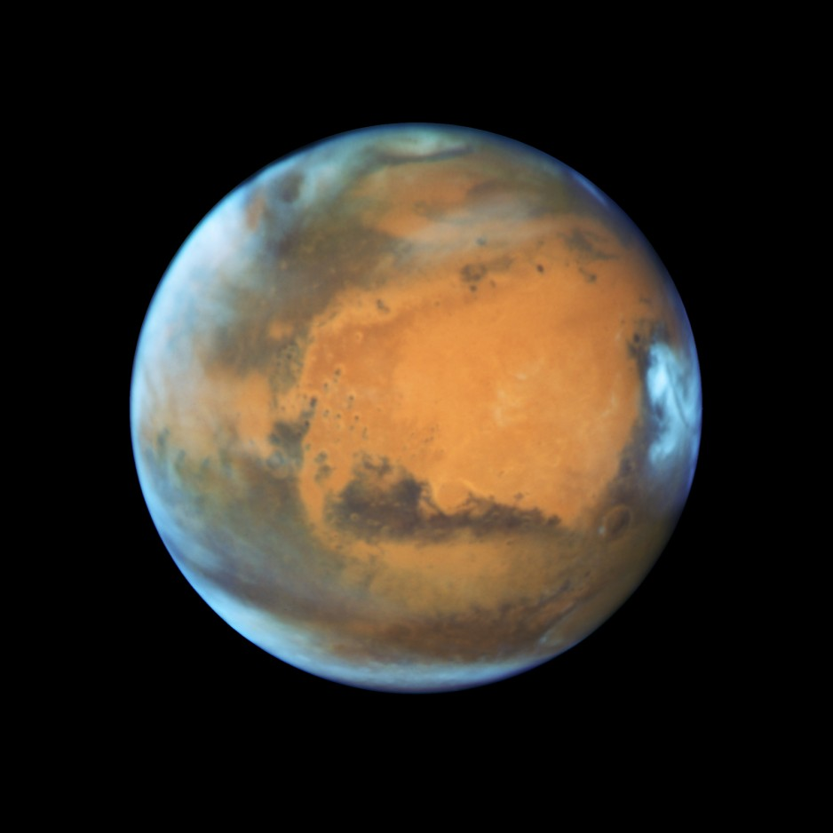 The planet Mars, captured by the Hubble Space Telescope. It shows a mostly reddish and brown surface, with some wispy white clouds. The ice cap is visible at the north pole, and some large craters are visible.