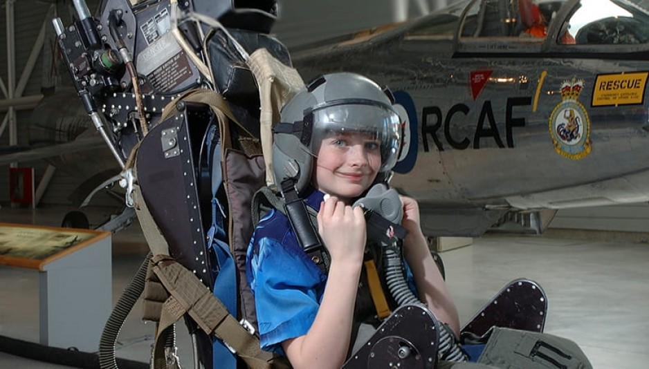 A young boy sitting in a pilot's seat which has been removed from the aircraft and is sitting on the floor of the museum