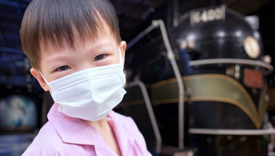 A young boy wearing a mask. In the background, you can see a locomotive from the museum in soft focus.