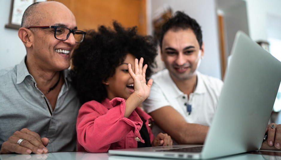 Two men and a young child smile as they sit at a table in front of a laptop; the child is waving at the screen