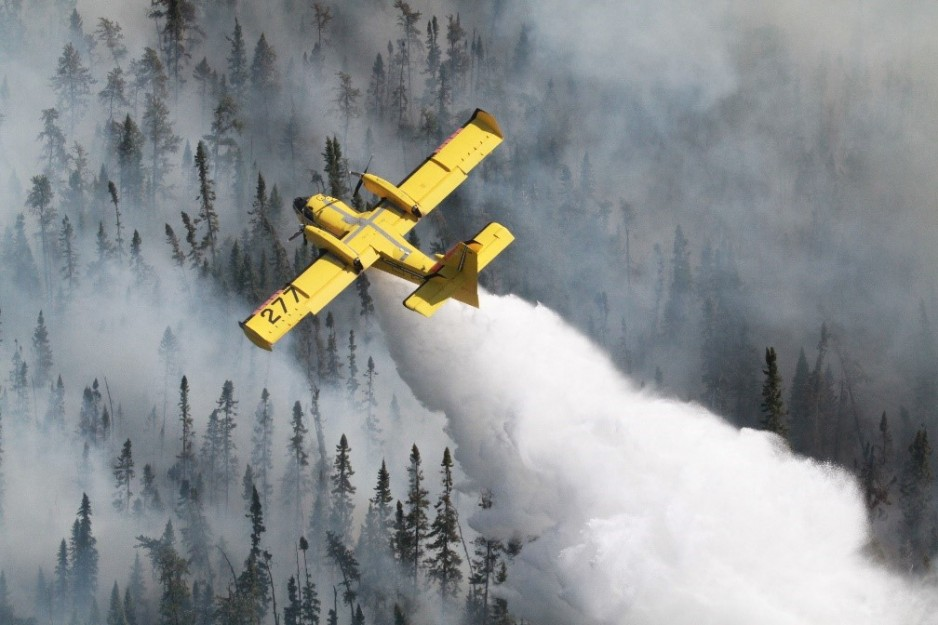 An aerial view of a bright yellow aircraft, a CL-415, flying over the treeline of a forest. The aircraft is spraying water below, while huge clouds of smoke billow over the trees.
