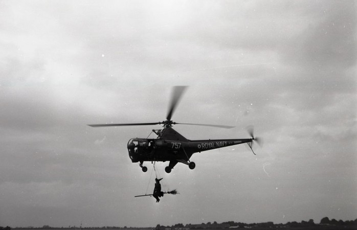 A Westland Dragonfly of the Royal Navy's Fleet Air Arm carrying a man dressed up as a witch for a special event, September 1962. CASM, Molson collection negative.