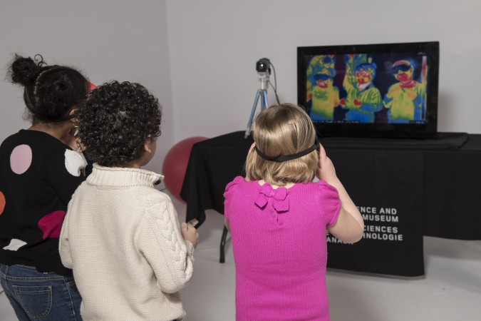 Photo of children looking at a thermal sensor