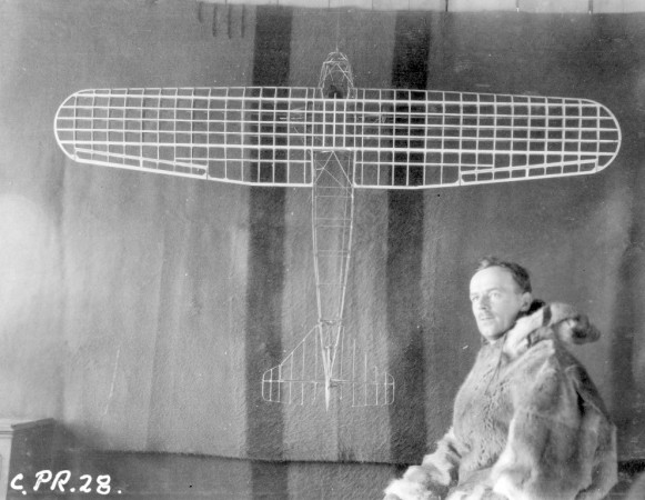 A member of the Hudson Strait Expedition sits beside a model aircraft.