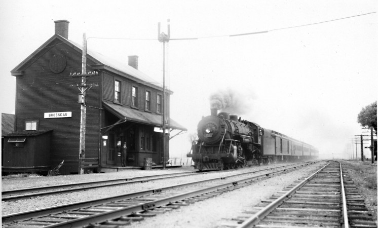 Black and white photograph showing a steam locomotive approaching a station.