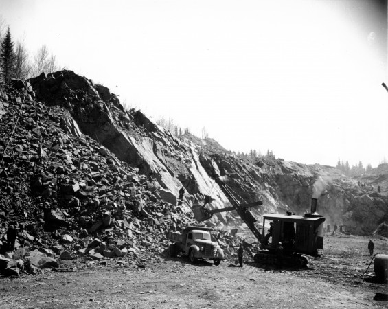 Loading iron ore which has been blasted from an entire hill of the same in Eastern Canada.