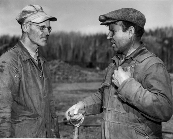 Two workers discuss  a day's outturn of iron ore from an emergency war mining project in Eastern Canada.