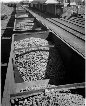 A trainload of iron ore at a Canadian National station in Eastern Canada en-route from an emergency war mining project to the steel mills at Sydney.