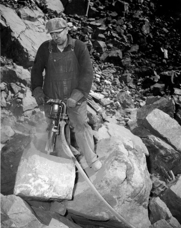 A man breaking large blocks of iron ore with an air drill, blasted from the face of a hill of ore in Eastern Canada so it will pass through the crusher.