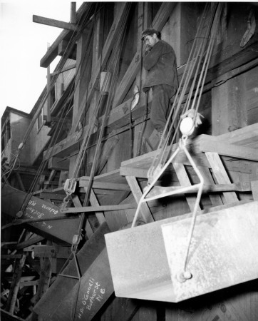 Loading iron ore into Canadian National cars at an emergency war mining project in Eastern Canada for transport to the steel mills at Sydney.