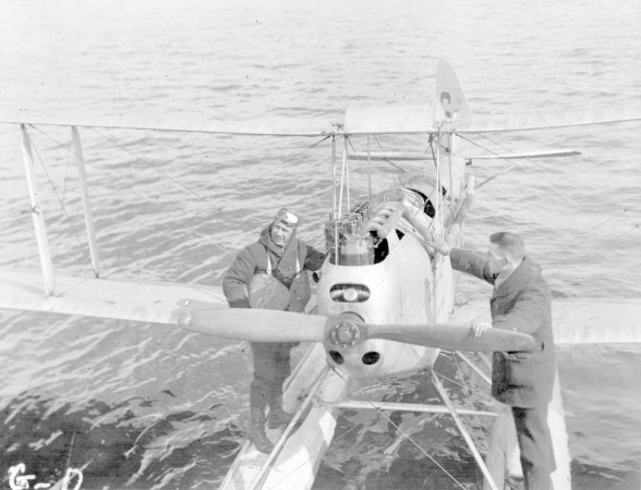 Black and white photograph of two Expedition members standing on pontoons of Moth plane.