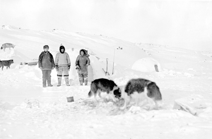 Black and white photograph of an Expedition member and two Inuits
