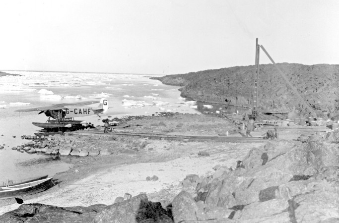 Black and white photograph showing an airplane being taken from the icy cove on a trolley