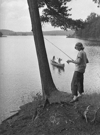 Woman with fishing rod near lake