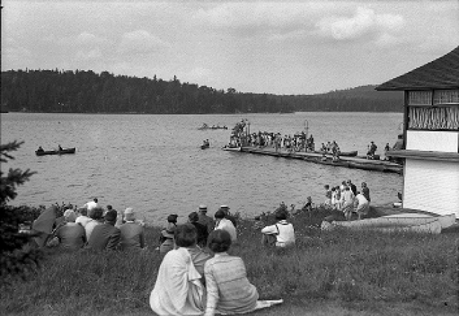 People on shore watching boating on lake