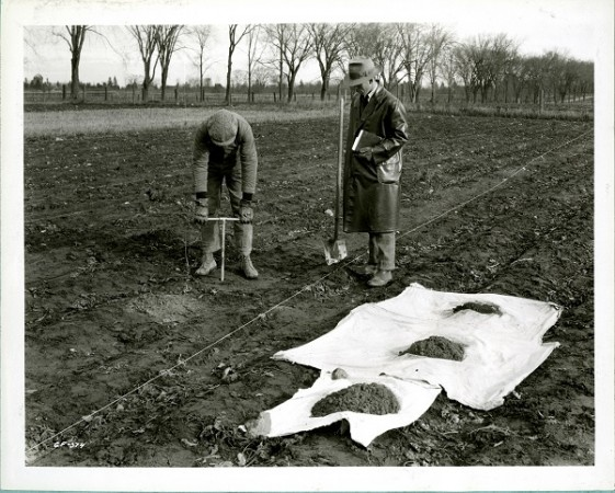 Two men stand in a dirt field; one bores into the soil while the other looks on.