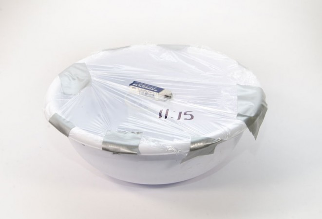 a bowl with saran-wrap on top and an eraser