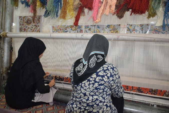 A mother and daughter weaving a carpet.