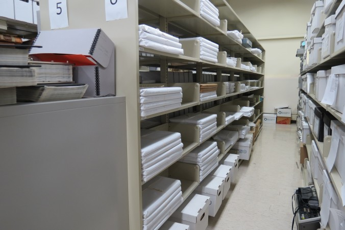 Shelf of ledgers wrapped in buffered paper for protection against dust and from handling over time.