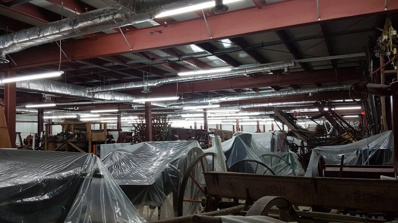 A series of carriages and farm equipment sit in a cramped warehouse.