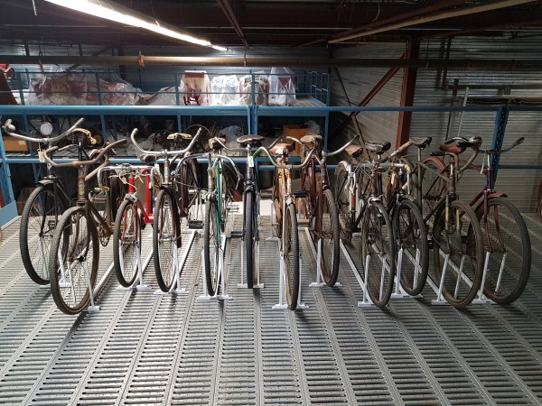 A series of bicycles stand in a line on a metal rack.
