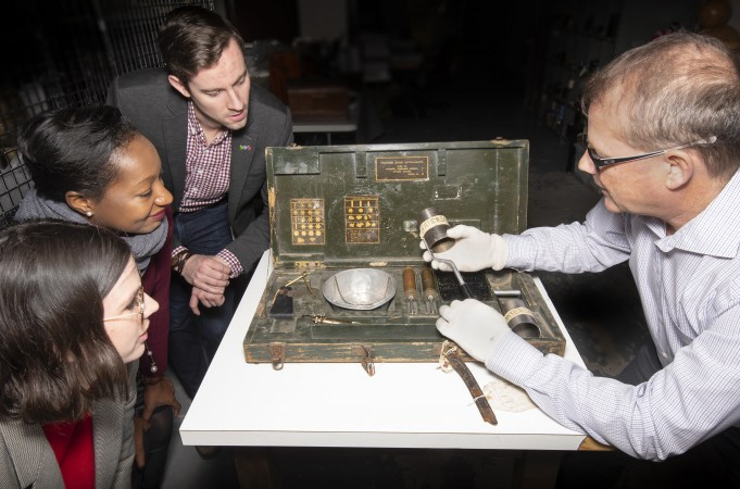 A group of three people listen as a curator speaks about an artifact.