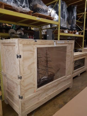 A large wooden crate displays a ship model through a clear panel.