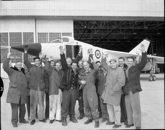 Photograph of pilot Jan Zurakowski and crew cheering in front of Avro Arrow RL-201