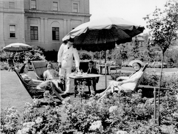 A family sitting on lawn furniture in the rose garden of the Nova Scotian hotel
