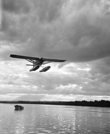 Bellanca CH-300 Pacemaker flying over a lake