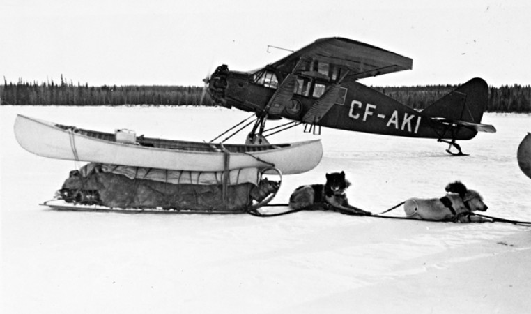 Bellanca CH-300 Pacemaker next to a kayak and a dog sled