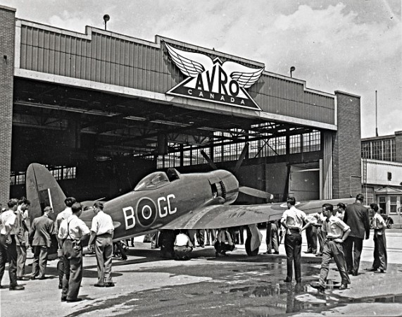 Avion Sea Fury FB.11 de Hawker devant un hangar