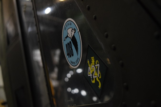 Squadron decals are displayed on the window of an aircraft.