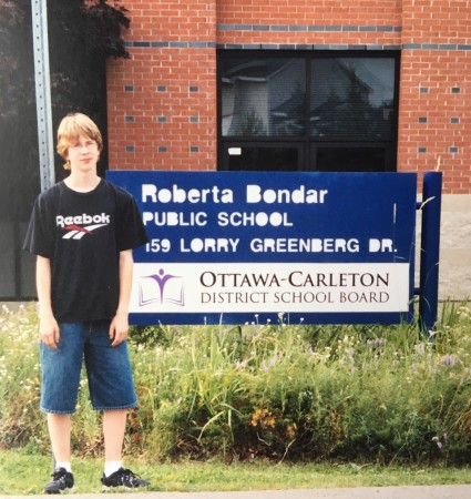 Nathaniel Whelan standing by the school's sign shortly following his grade 8 graduation.