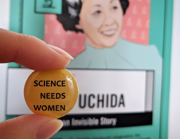 A pin with the words 'Science Needs Women' being held up in front of a Women in STEM Poster of Irene Ayako Uchida.