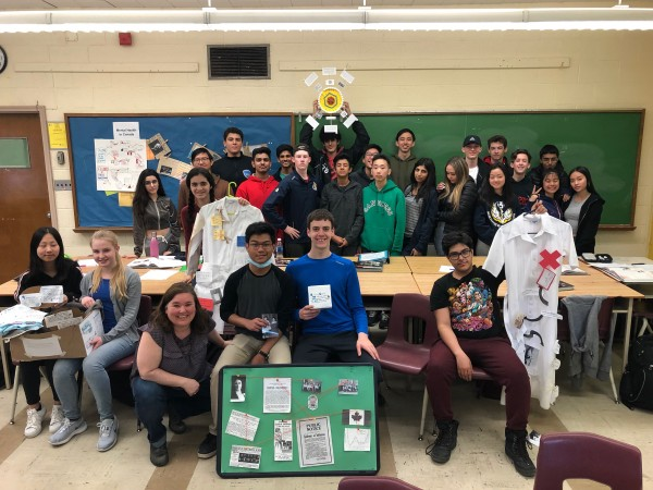 A group of students poses with their winning project in the classroom.